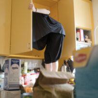 Kuvassa henkilö on kiivennyt tiskipyödälle seisomaan ja ylävartalo on keltaisessa tiskikaapissa. Etualalla pikaruokapaikan paperipussi, maitopurkki ja teerasia.